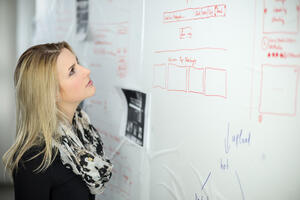 woman-looking-at-whiteboard-checking-workflow-brainstorming-and-to-do-list-for-new-ideas-and_t20_yvj6E0